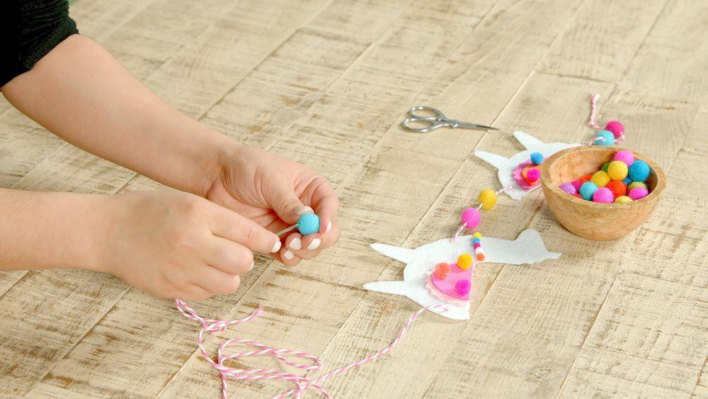Aleene's DIY Felt Llama Garland - thread felt balls onto twine