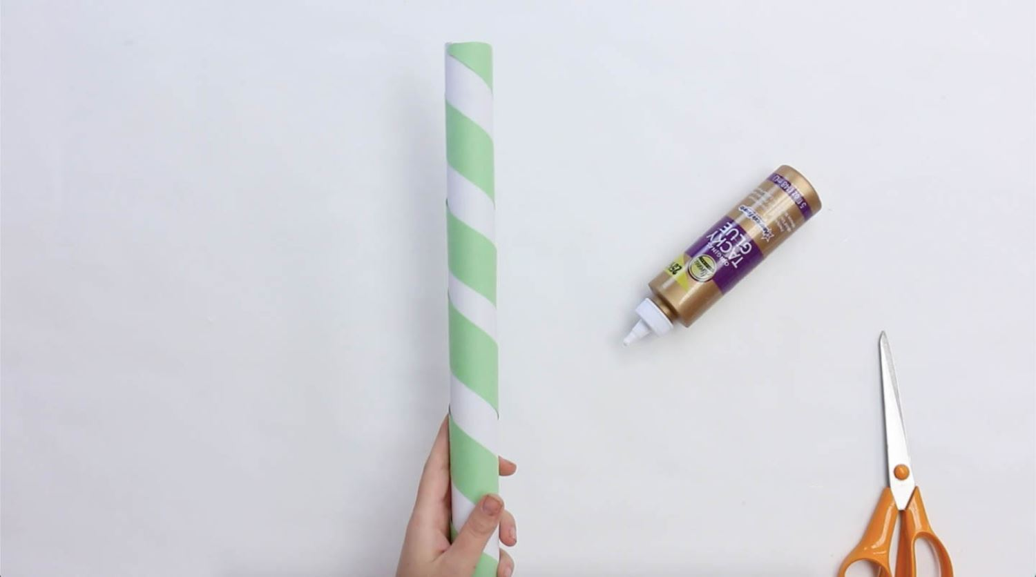 Glue strips of paper around tube