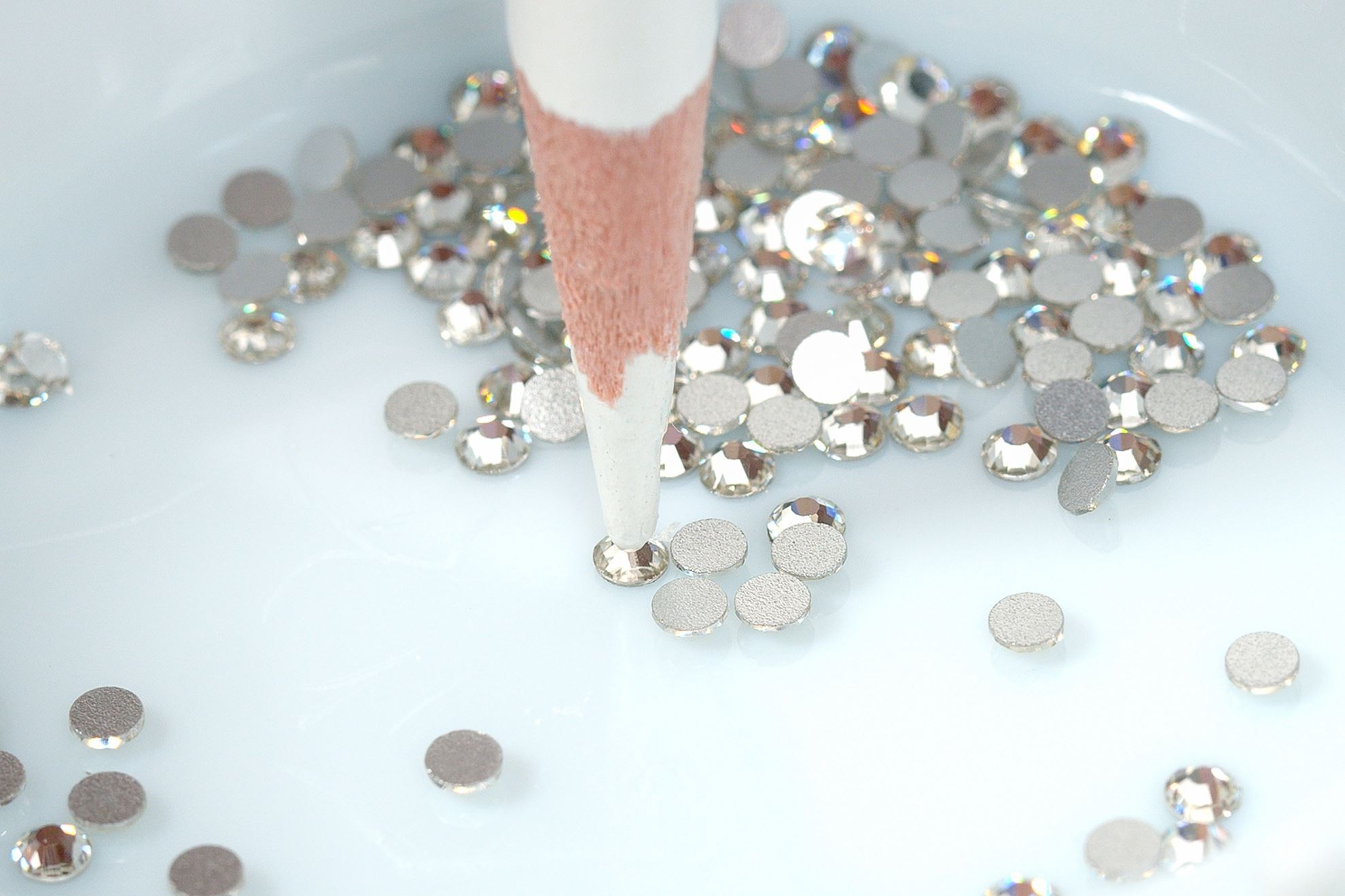 Use tip of colored pencil to grab rhinestones