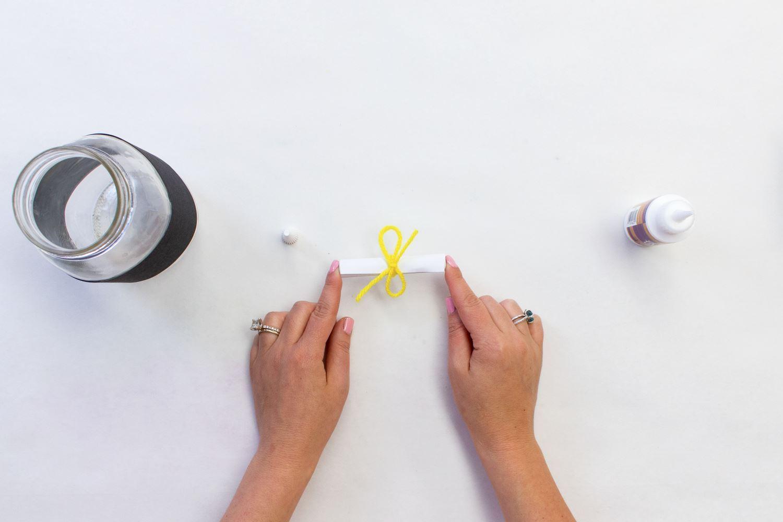 Tie yarn around paper roll