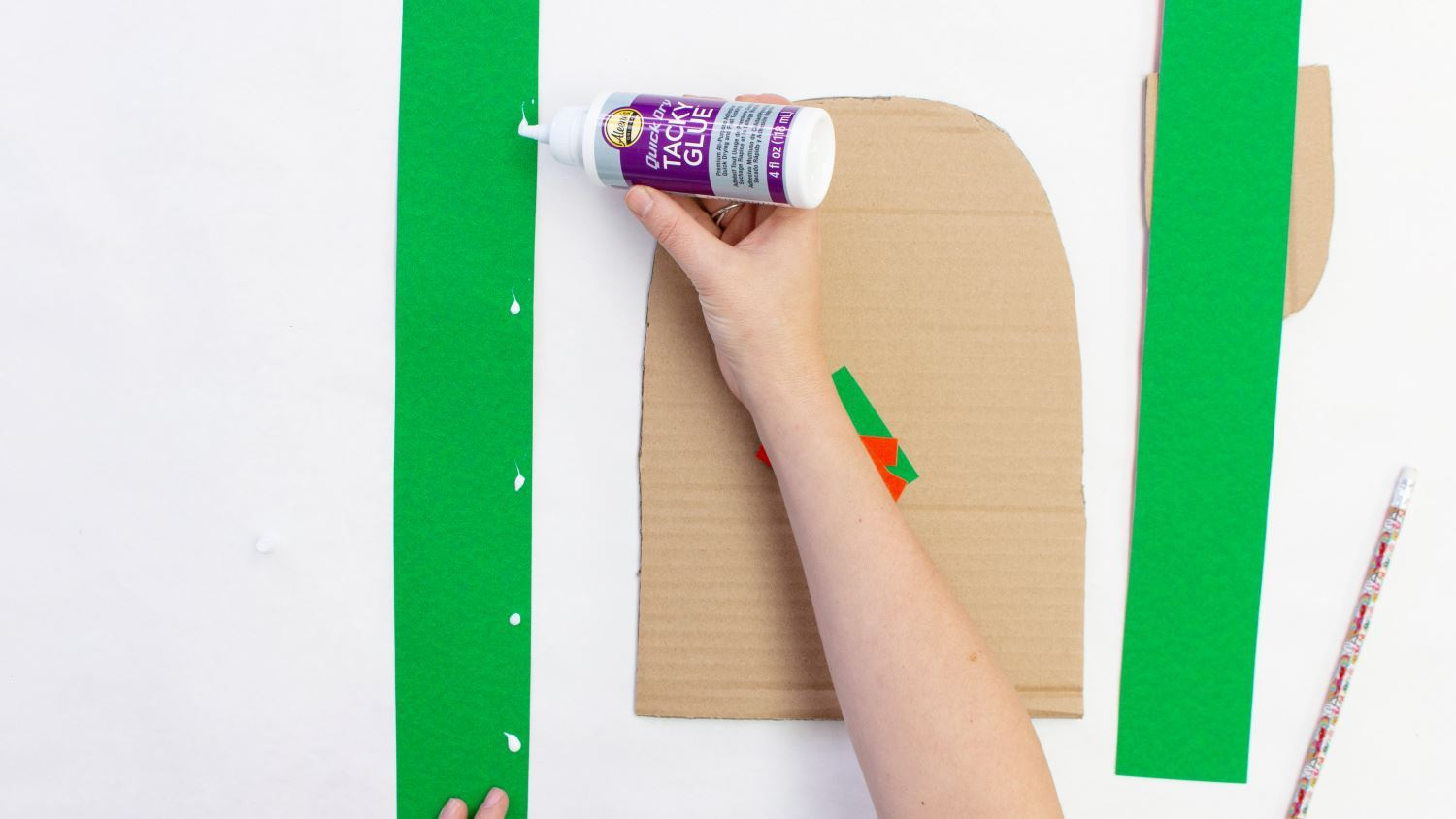Cut strips of poster board to frame cardboard