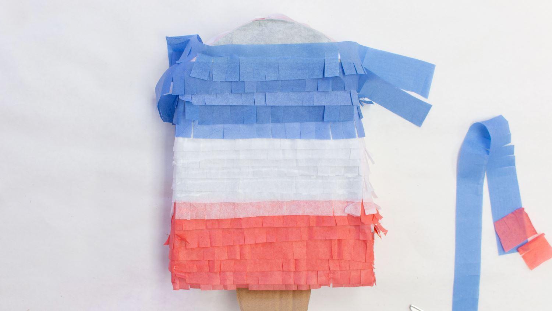 Glue tissue paper fringe around popsicle