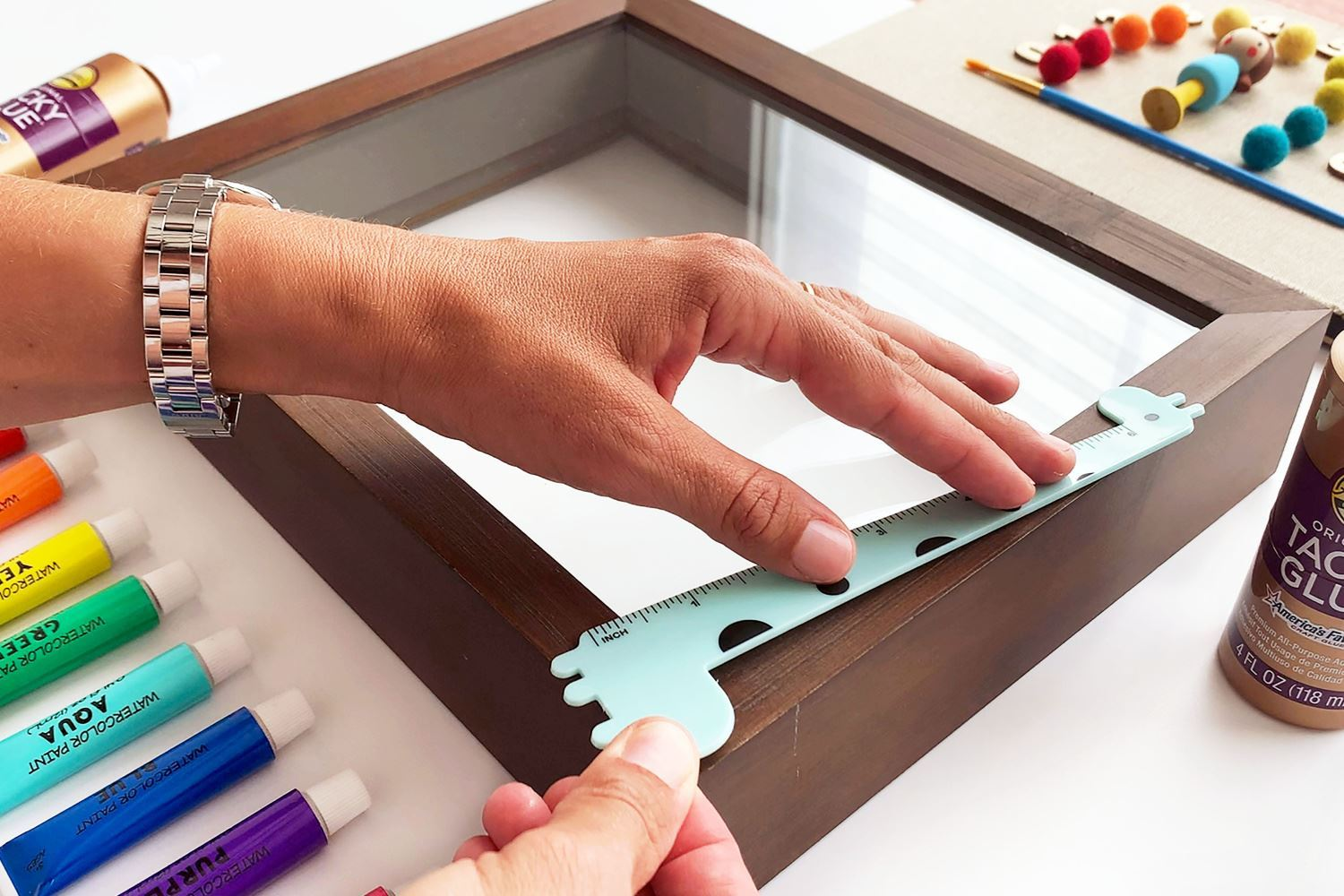 Continue gluing school-themed items to frame